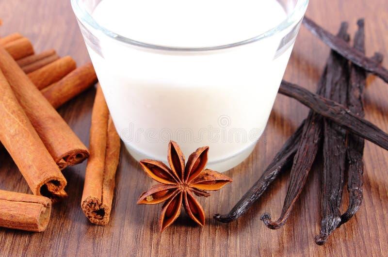 Душистые ваниль, ручки циннамона, анисовка звезды и стекло молока на деревянной поверхности стоковые изображения