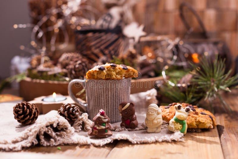 Душистый кофе, шоколады в форме диаграмм рождества Печенья и горячий напиток на праздник Уютная атмосфера, свечи стоковое изображение