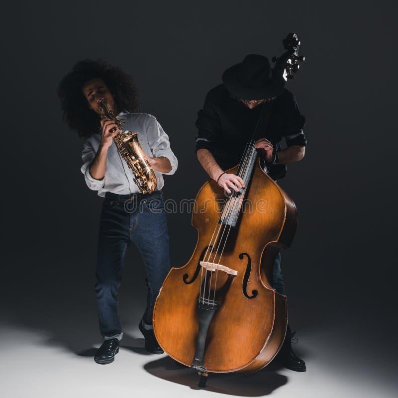 дуэт молодых джазменов играя трубу и саксофон стоковые изображения