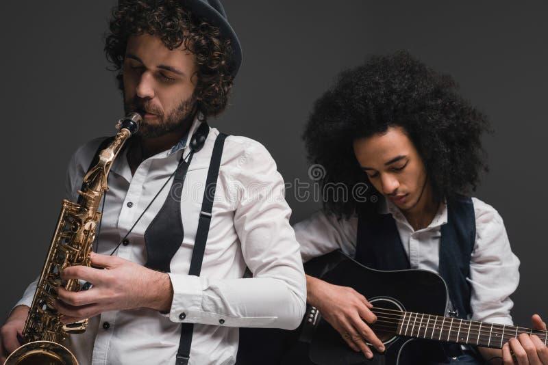 дуэт музыкантов играя саксофон и гитару стоковая фотография rf