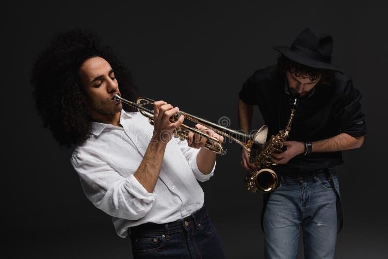 дуэт музыкантов играя трубу и саксофон стоковое фото rf