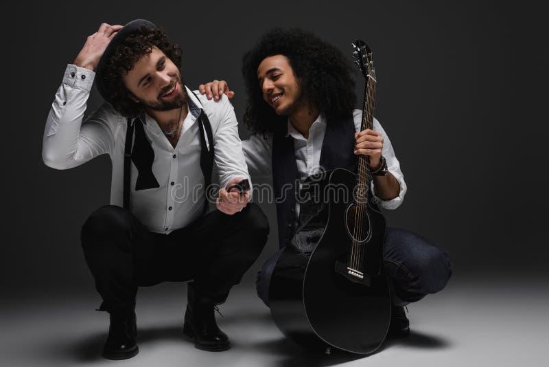 дуэт счастливых музыкантов с гитарой и губной гармоникой стоковые фотографии rf