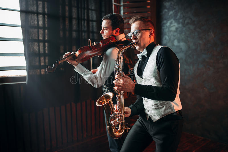 Дуэт человека и скрипача саксофона играя классическую мелодию стоковое фото