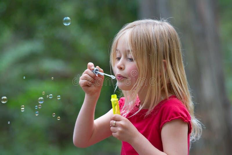 дуя девушка пузырей стоковое изображение