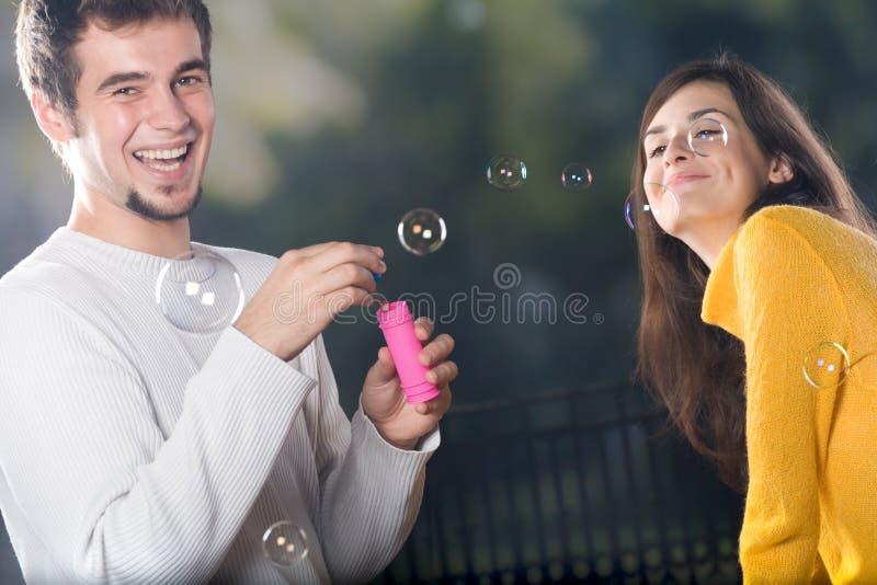 дуя пузыри соединяют outdoors ся детенышей стоковые изображения rf