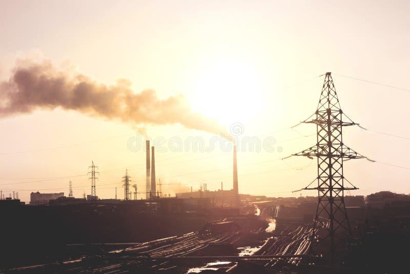 Дым загрязнения воздуха от труб и фабрика с предпосылкой захода солнца стоковое фото