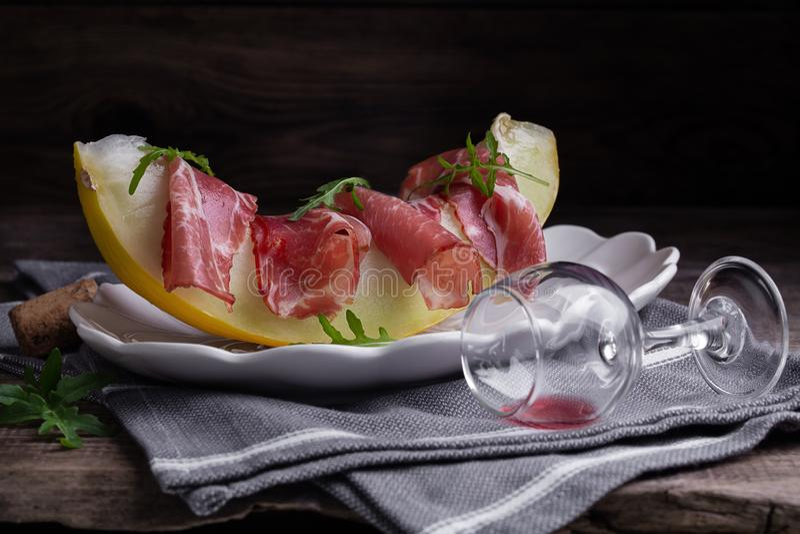 Дыня с ветчиной, arugula и красным вином стоковые фото