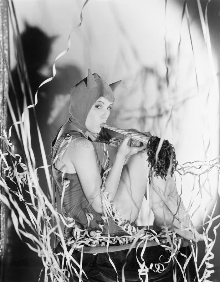 Дьявол партии, молодая женщина дует ее собственный рожок (все показанные люди более длинные живущие и никакое имущество не сущест стоковые изображения