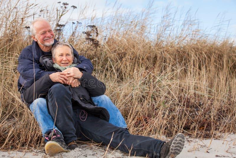 Дюны Балтийского моря счастливых зрелых пар расслабляющие стоковая фотография