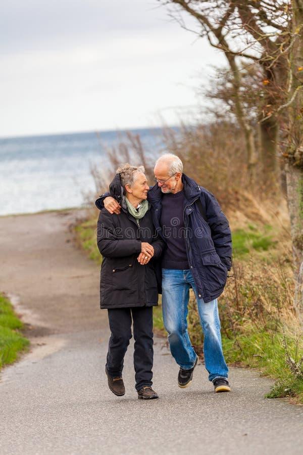 Дюны Балтийского моря счастливых зрелых пар расслабляющие стоковая фотография rf