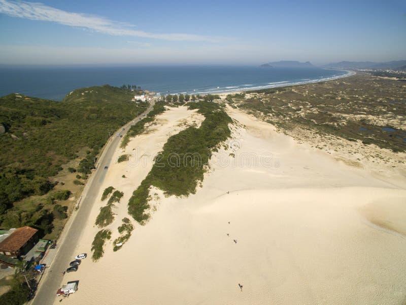Дюны в солнечном дне - пляж вида с воздуха Joaquina - Florianopolis - Санта-Катарина - Бразилия Июль 2017 стоковое фото