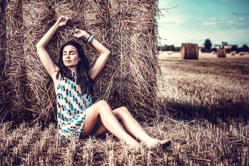 Длинная девушка волос ослабляя на стоге сена стоковое изображение rf