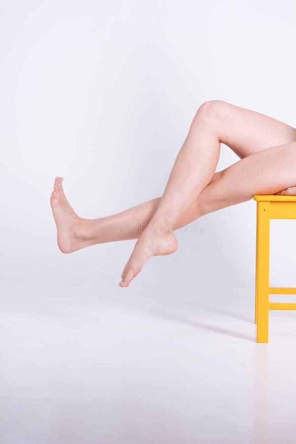 Длинная женщина ног сидит на белой предпосылке Депиляция стоковые фото
