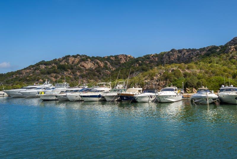 Длинная пристань с рекреационными шлюпками флота Марина курорта Poltu Quatu, Сардиния стоковые фото