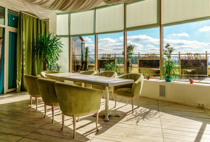 Длинная таблица с креслами в пастельном ресторане ожидает гостей Взгляд окружающего солнечного света внутренний с большим окном стоковые изображения rf
