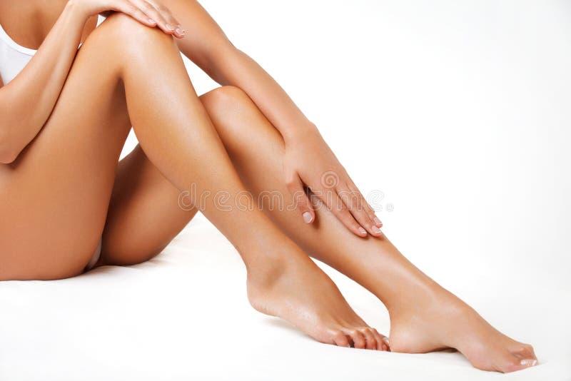 Длинные ноги женщины изолированные на белизне. Женские ноги после депиляции стоковая фотография rf