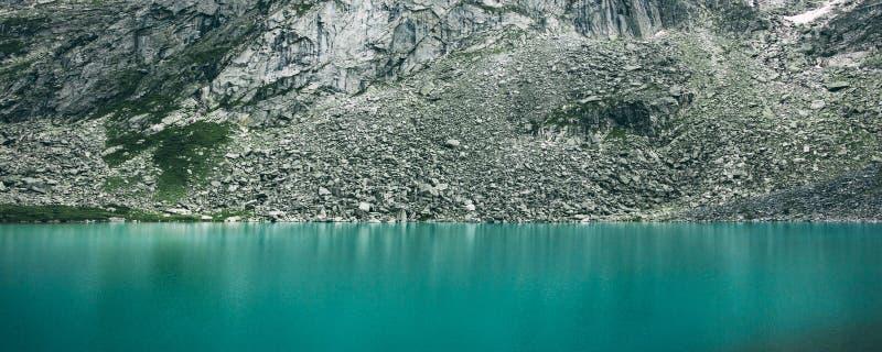 Длинный горизонтальный обваловка камня фото на береге озера горы стоковое изображение