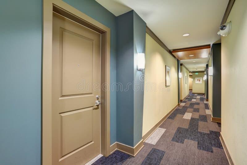 Длинный голубой коридор с полом ковра в жилом доме стоковые изображения