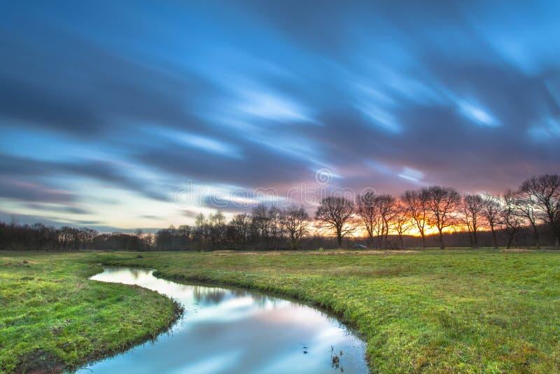Длинный заход солнца Exposue с запачканными облаками над ландшафтом реки стоковая фотография rf