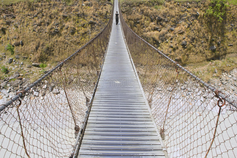 Длинный пешеходный мост с идя женщиной, мост над рекой горы, стоковые изображения