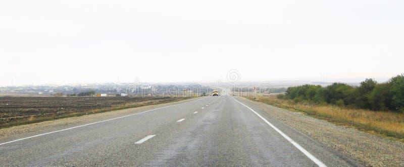 Длинный прямой ландшафт шоссе с moving автомобилями на дневном времени стоковое изображение rf