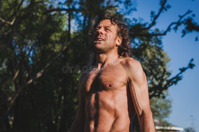 Длинный с волосами спортсмен получая готовый для бежать стоковое изображение