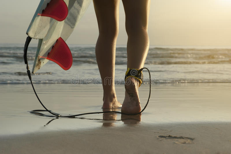 Длинный угол серфера идя вдоль пляжа с ребрами поводка и доски лодыжки стоковое изображение