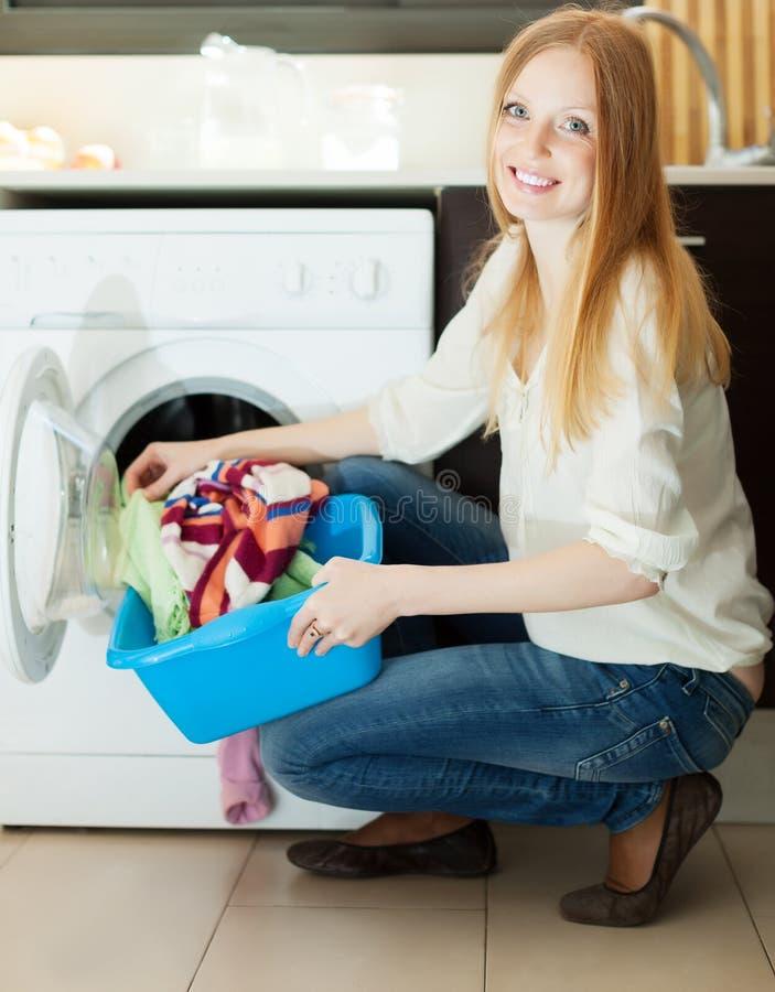 Длинн-с волосами белокурая женщина используя стиральную машину стоковые фотографии rf