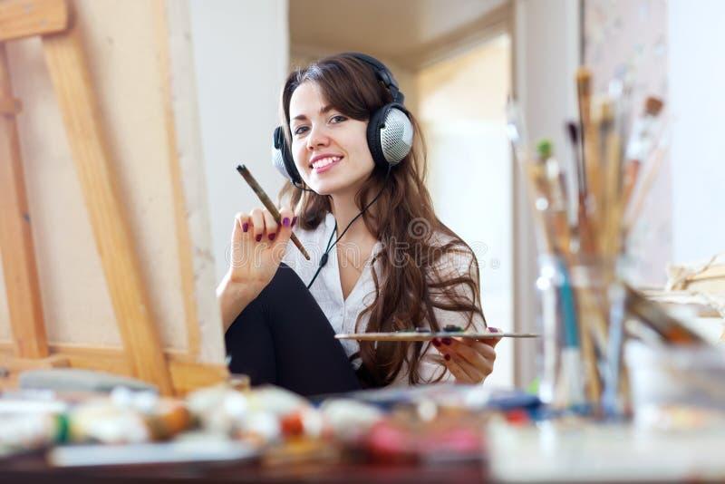 Длинн-с волосами девушка в красках наушников на холсте стоковое изображение rf