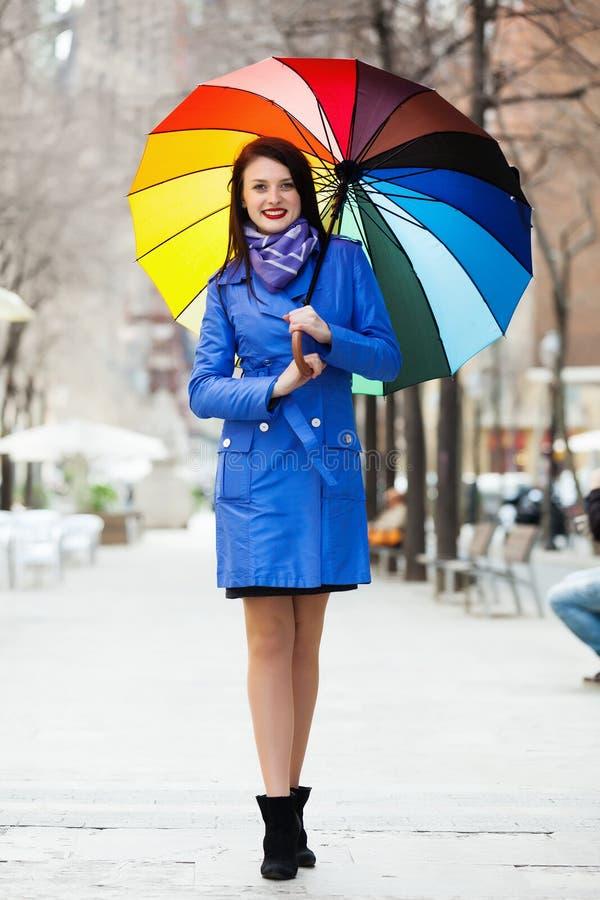 Длинн-с волосами девушка в плаще с зонтиком стоковые изображения