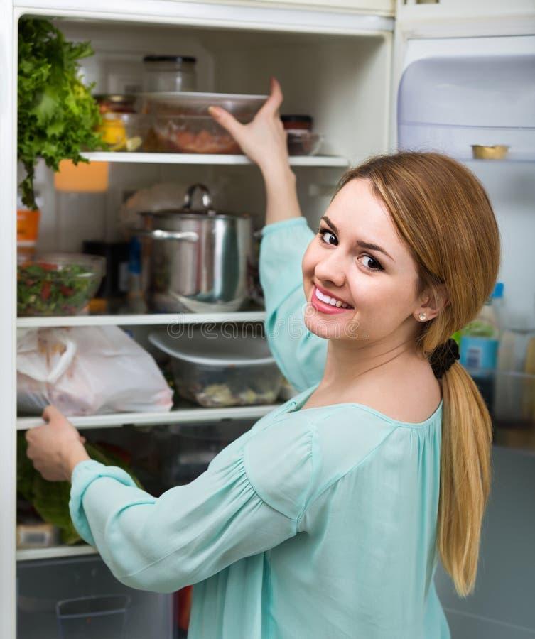 Длинн-с волосами женщина аранжируя космос в холодильнике дома стоковое изображение