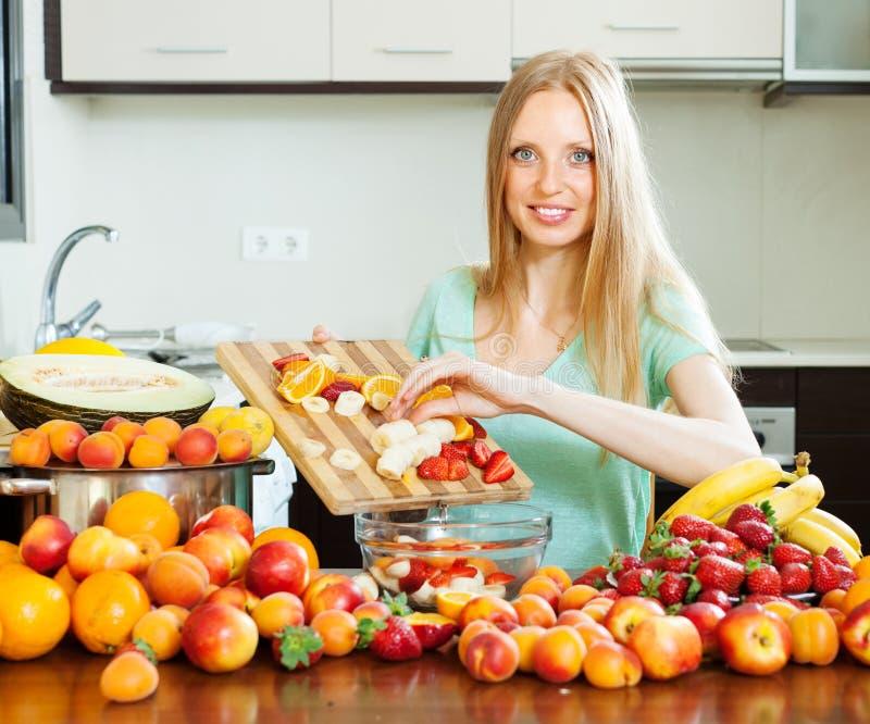 Длинн-с волосами женщина варя фруктовый салат стоковое изображение