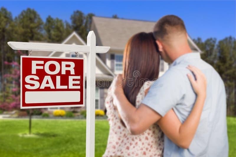 Для продажи знак недвижимости, воинская пара смотря дом стоковое фото rf
