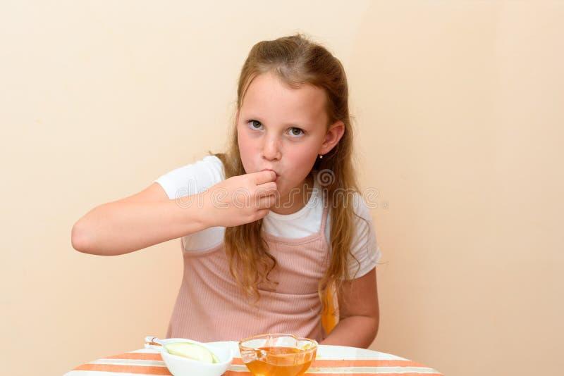 Еврейская девушка окуная куски яблока в мед на Rosh HaShanah стоковые фотографии rf