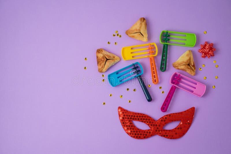 Еврейская предпосылка Purim праздника с hamantaschen печенья, noisemaker и маска масленицы стоковые изображения rf