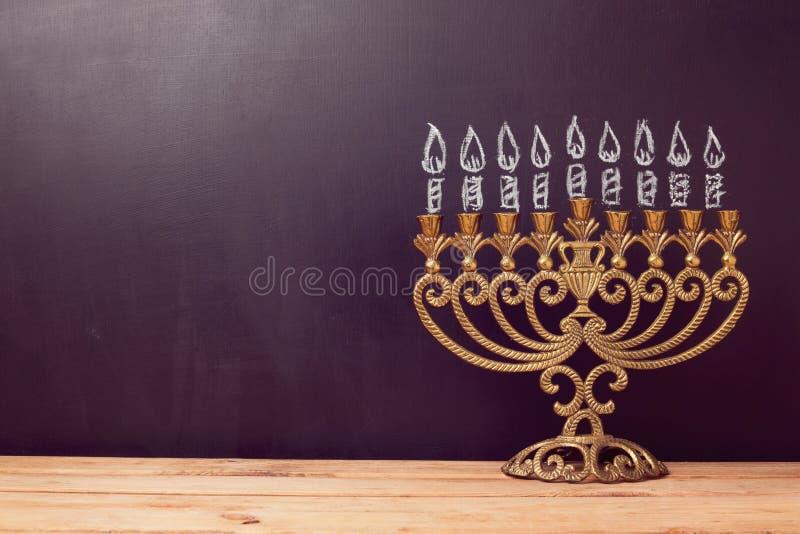 Еврейская предпосылка Хануки праздника с menorah над доской с чертежом руки