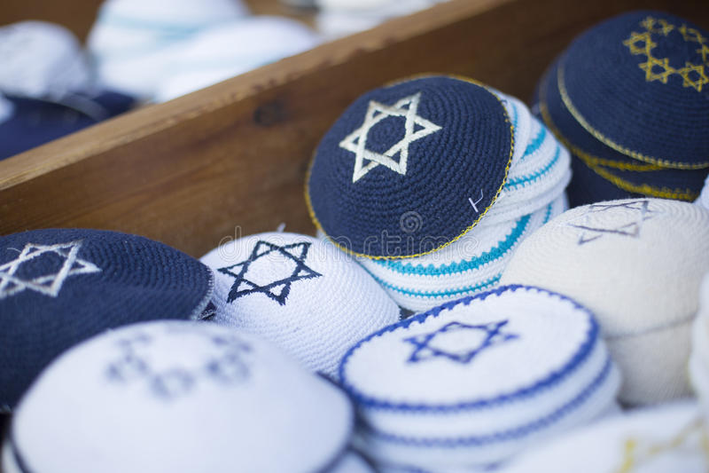 Еврейские религиозные крышки (yarmulke) на каменной мостоваой около сувенирного магазина в еврейском квартале старого города стоковые изображения