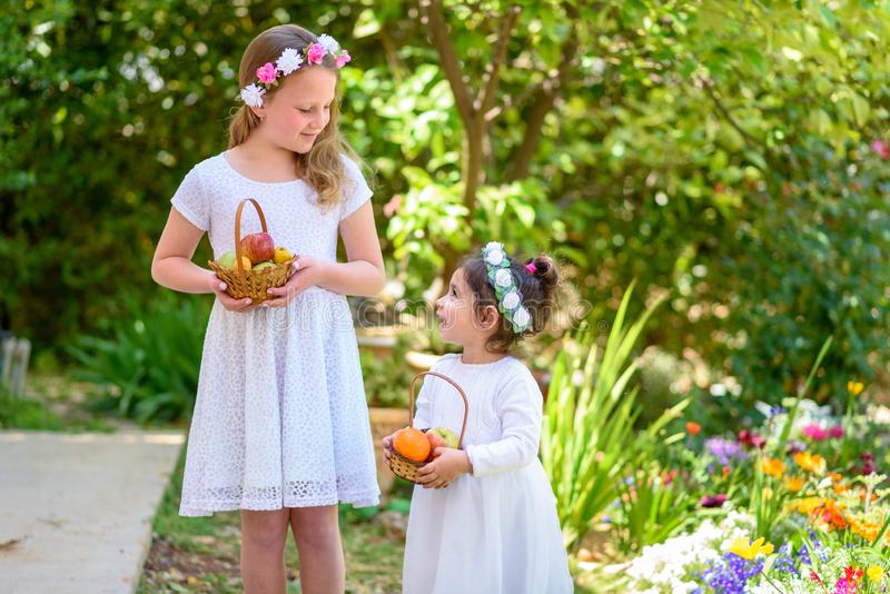 Еврейский праздник Shavuot Маленькие девочки HarvestTwo в белом платье держат корзину со свежими фруктами в саде лета стоковые изображения