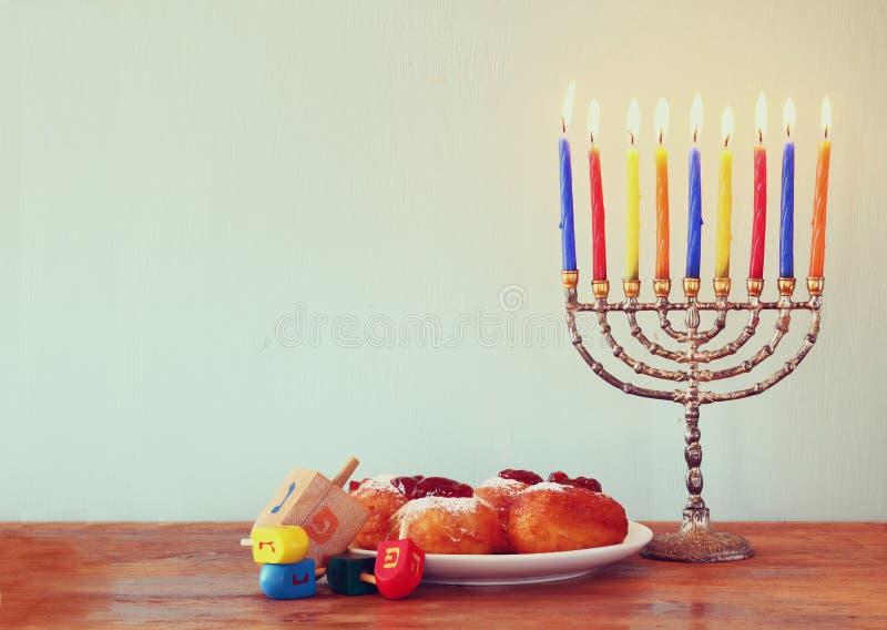 Еврейский праздник Ханука с menorah, донутами над деревянным столом ретро фильтрованное изображение