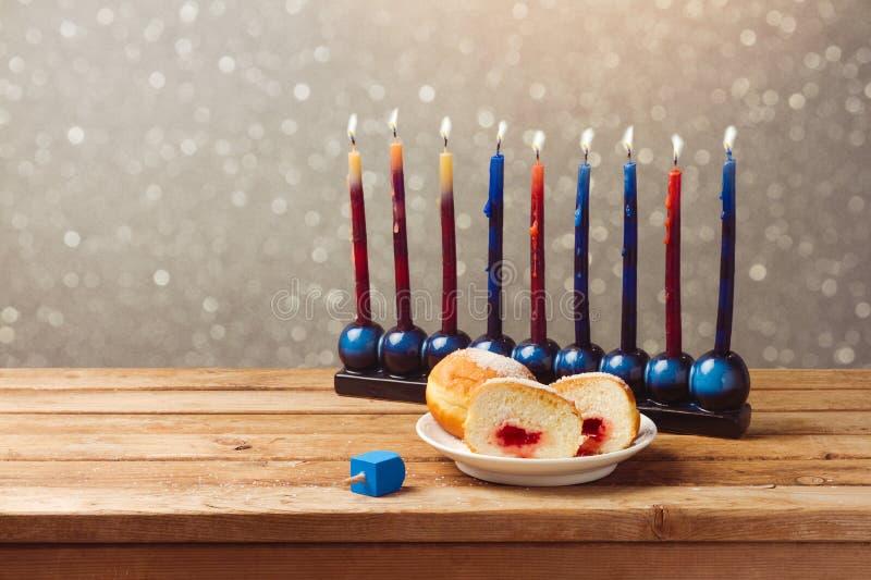 Еврейский праздник Ханука с sufganiyah и menorah на деревянном столе над предпосылкой bokeh
