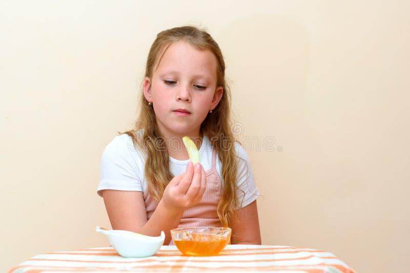 Еврейский ребенок окуная куски яблока в мед на Rosh HaShanah стоковые изображения