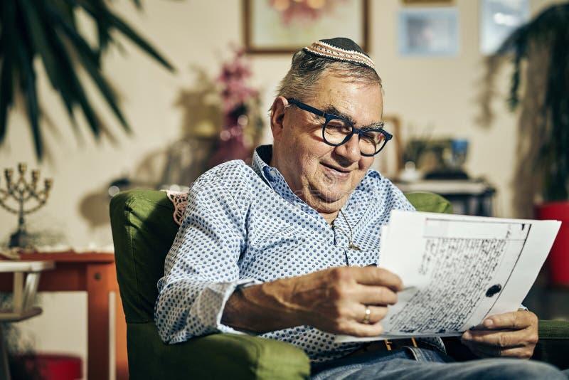 Еврейский старший со стеклами в кресле читая книгу torah стоковые фото