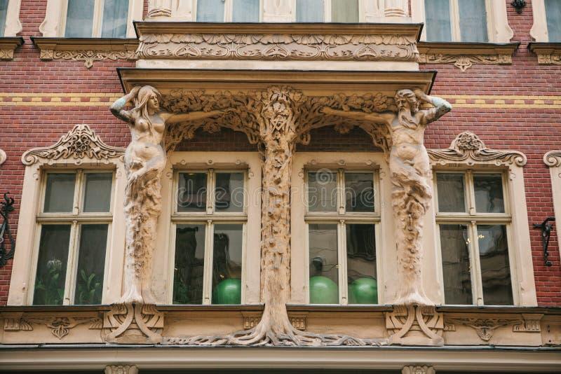 Европейская архитектура Конец-вверх - скульптуры - столбцы в форме античных характеров поддерживая балкон - фасад  стоковые фото