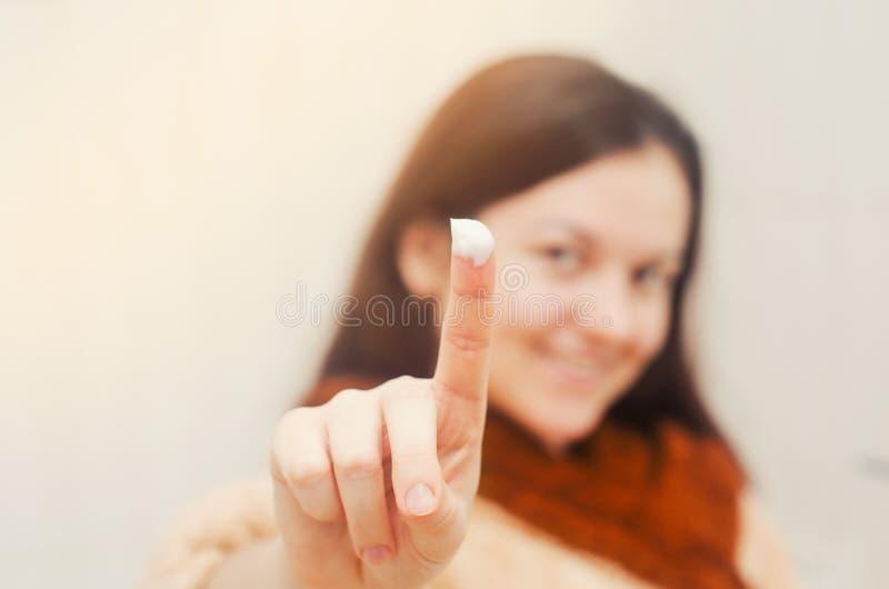 Европейская девушка брюнет, палец в cream концепции красоты Изолированная предпосылка стоковая фотография rf