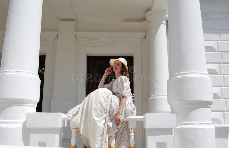 Европейская женщина сидя в солнечности и касающей шляпе в винтажном платье около дворца стоковое фото