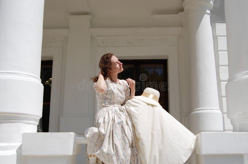 Европейская женщина сидя в солнечности и касающих волосах в винтажном платье около дворца стоковая фотография