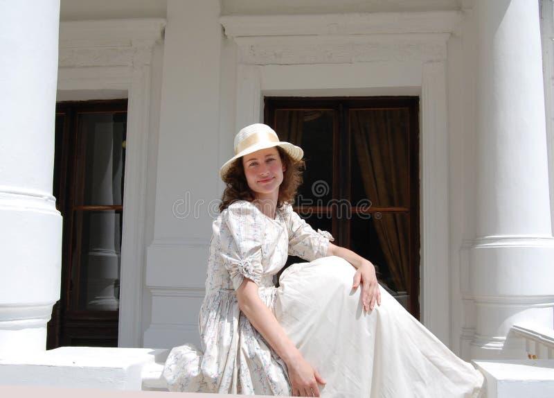 Европейская женщина сидя в солнечности и касающих волосах в винтажном платье около дворца стоковое фото rf