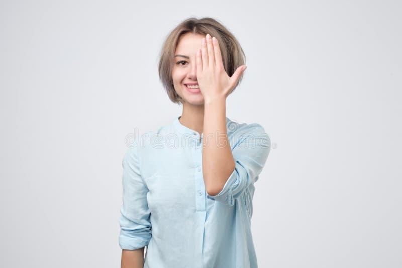 Европейская молодая женщина в голубой рубашке закрывая один глаз с рукой и усмехаться стоковое фото rf