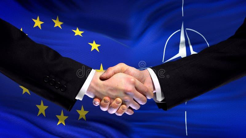 Европейский союз и рукопожатие НАТО, международное приятельство, предпосылка флага стоковое изображение rf