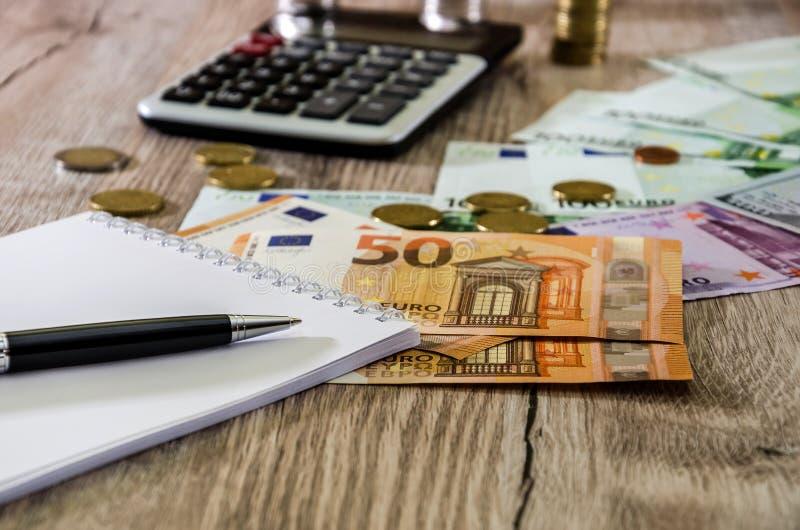 Евро, доллары, монетки, тетрадь, ручка и калькулятор на деревянном конце предпосылки вверх стоковое изображение